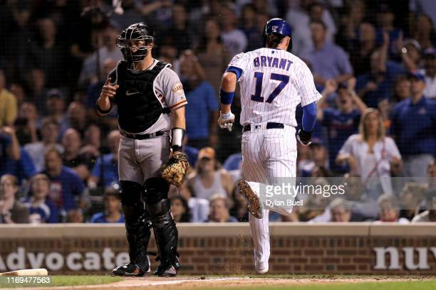 Kris Bryant of the Chicago Cubs scores a run past Stephen Vogt of the San Francisco Giants in the sixth inning at Wrigley Field on August 21 2019 in...