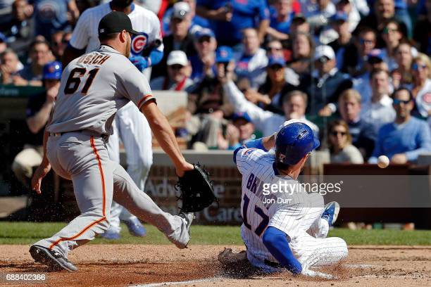Kris Bryant of the Chicago Cubs scores on a wild pitch as Josh Osich of the San Francisco Giants is unable to catch the ball after a throwing error...