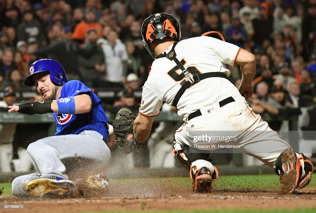 Kris Bryant #17 of the Chicago Cubs scores sliding into home plate before the throw to Nick Hundley #5 of the San Francisco Giants in the top of the eighth inning at AT&T Park on August 8, 2017 in San Francisco, California. The Giants won the game 5-3.
