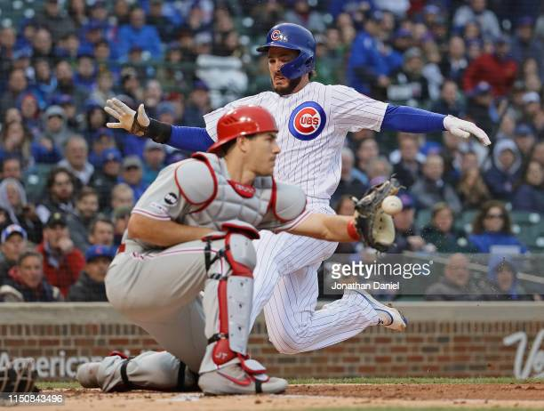 Kris Bryant of the Chicago Cubs slides in to score a run as JT Realmuto of the Philadelphia Phillies takes the throw in the 1st inning at Wrigley...