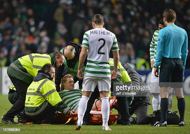 Kris Commons of Celtic is carried off during the UEFA Champions League Group G match between Celtic and FC Spartak Moscow at Celtic Park on December...