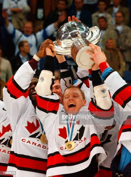 Kris Draper of Canada hoists the trophy with teammates after a 3-2 overtime win over Sweden in the Gold Medal game of the 2003 IIHF World Hockey...