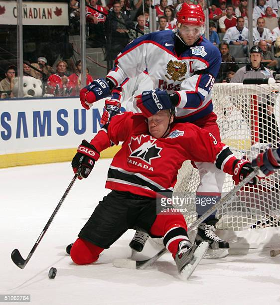 Kris Draper of Team Canada is hauled to the ice by Alexei Yashin of Team Russia during the first period of their game in the World Cup of Hockey on...