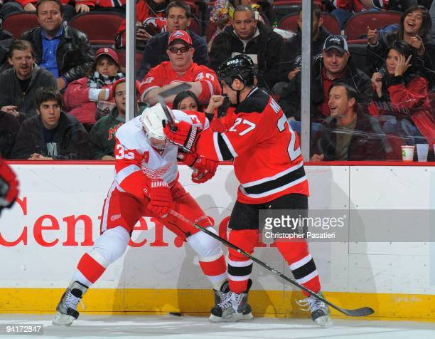 Kris Draper of the Detroit Red Wings and Mike Mottau of the New Jersey Devils play for possession of the puck along the boards during the third...