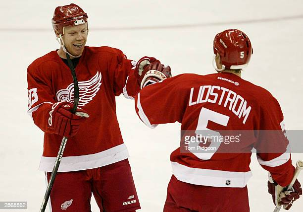 Kris Draper of the Detroit Red Wings congratulates teammate Nicklas Lidstrom after his goal in the third period against the Chicago Blackhawks at Joe...