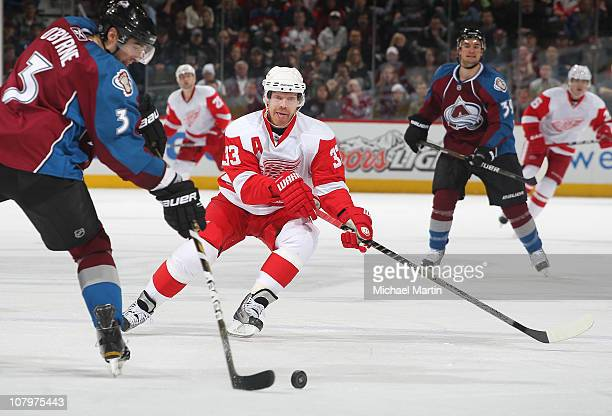 Kris Draper of the Detroit Red Wings defends against Ryan O'Byrne of the Colorado Avalanche at the Pepsi Center on January 10 2011 in Denver Colorado...