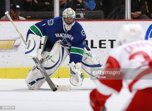 Kris Draper of the Detroit Red Wings looks for a rebound as Roberto Luongo of the Vancouver Canucks makes a save during their game at General Motors...