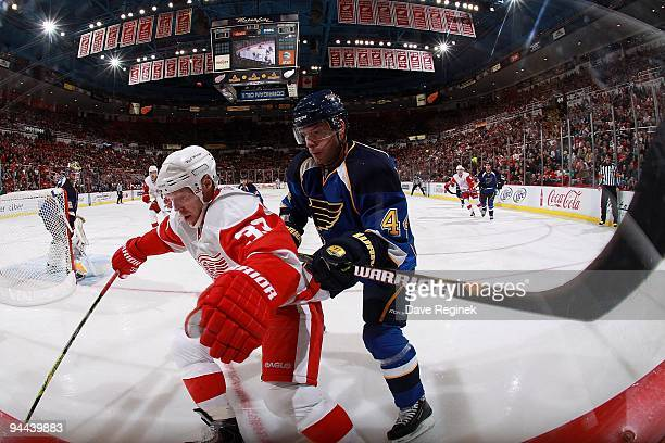 Kris Draper of the Detroit Red Wings protects the puck from Darryl Sydor of the St. Louis Blues during a NHL game at Joe Louis Arena on December 9,...