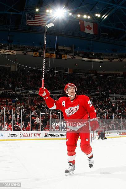 Kris Draper of the Detroit Red Wings raises his stick to the cheering crowd after being named one of the stars of the game after an NHL game against...