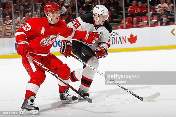 Kris Draper of the Detroit Red Wings skates alongside Anton Volchenkov of the New Jersey Devils during an NHL game at Joe Louis Arena on January 26...
