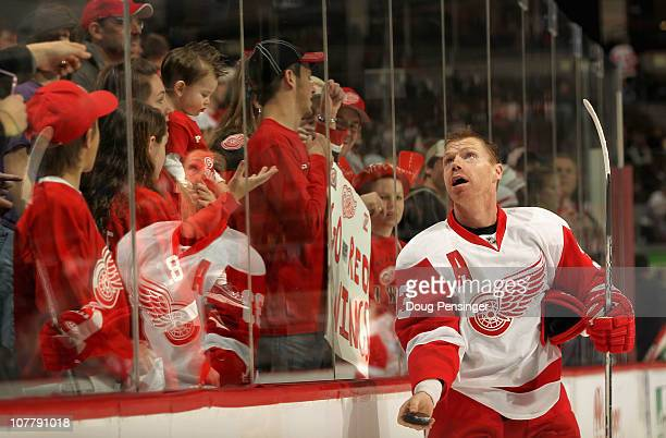 Kris Draper of the Detroit Red Wings tosses a puck to the fans during warm ups as they prepare to face the Colorado Avalanche at the Pepsi Center on...