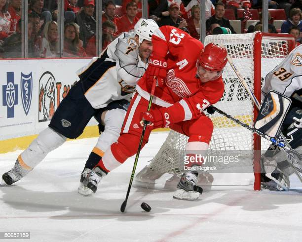 Kris Draper of the Detroit Red Wings tries the wraparound with Greg de Vries of the Nashville Predators in tow during game two of the 2008 NHL...