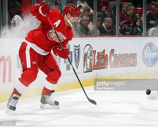Kris Draper of the Detroit Red Wings tries to control the puck behind the net during a NHL game against the Colorado Avalanche at Joe Louis Arena on...