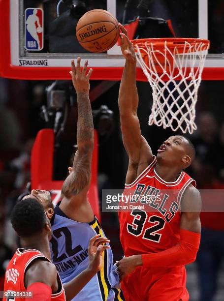 Kris Dunn of the Chicago Bulls blocks a shot by Xavier RathanMayes of the Memphis Grizzlies at the United Center on March 7 2018 in Chicago Illinois...