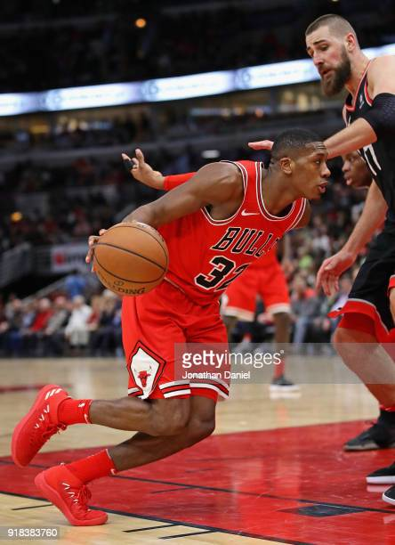 Kris Dunn of the Chicago Bulls drives against Jonas Valanciunas of the Toronto Raptors at the United Center on February 14 2018 in Chicago Illinois...