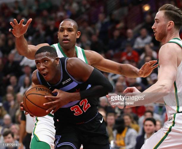 Kris Dunn of the Chicago Bulls drives between Al Horford and Gordon Hayward of the Boston Celtics at the United Center on February 23 2019 in Chicago...