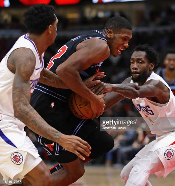 Kris Dunn of the Chicago Bulls drives between Lou Williams and Patrick Beverley of the LA Clippers at the United Center on January 25, 2019 in...