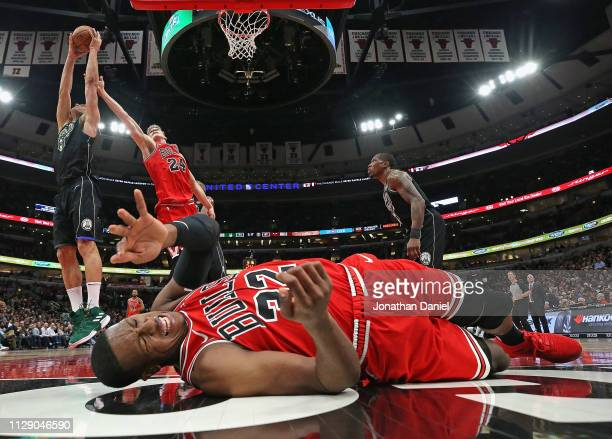 Kris Dunn of the Chicago Bulls hits the floor hard as Brook Lopez of the Milwaukee Bucks and Lauri Markkanen battle for a rebound at the United...