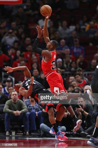 Kris Dunn of the Chicago Bulls is called for a charge as he tries to shoot against Kyle Lowry of the Toronto Raptors at the United Center on December...