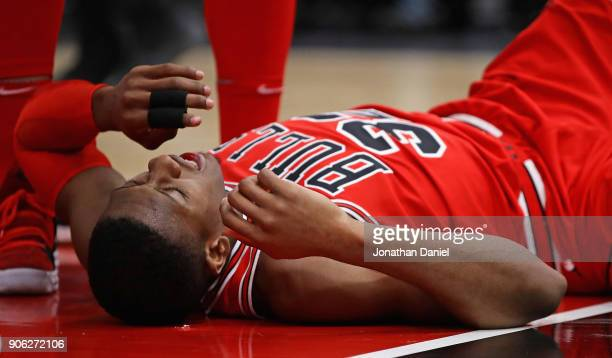 Kris Dunn of the Chicago Bulls lays on the floor after suffering a mouth injury following a dunk against the Golden State Warriors at the United...