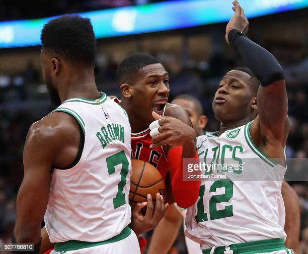 Kris Dunn of the Chicago Bulls tries to squeeze between Jaylen Brown and Terry Rozier of the Boston Celtics at the United Center on March 5 2018 in...