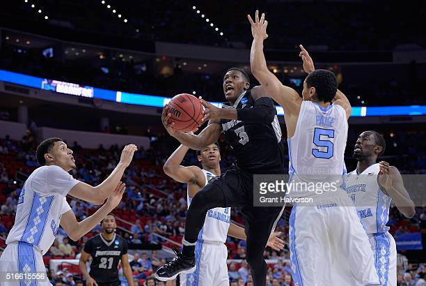 Kris Dunn of the Providence Friars shoots against Marcus Paige and Justin Jackson of the North Carolina Tar Heels in the second half during the...
