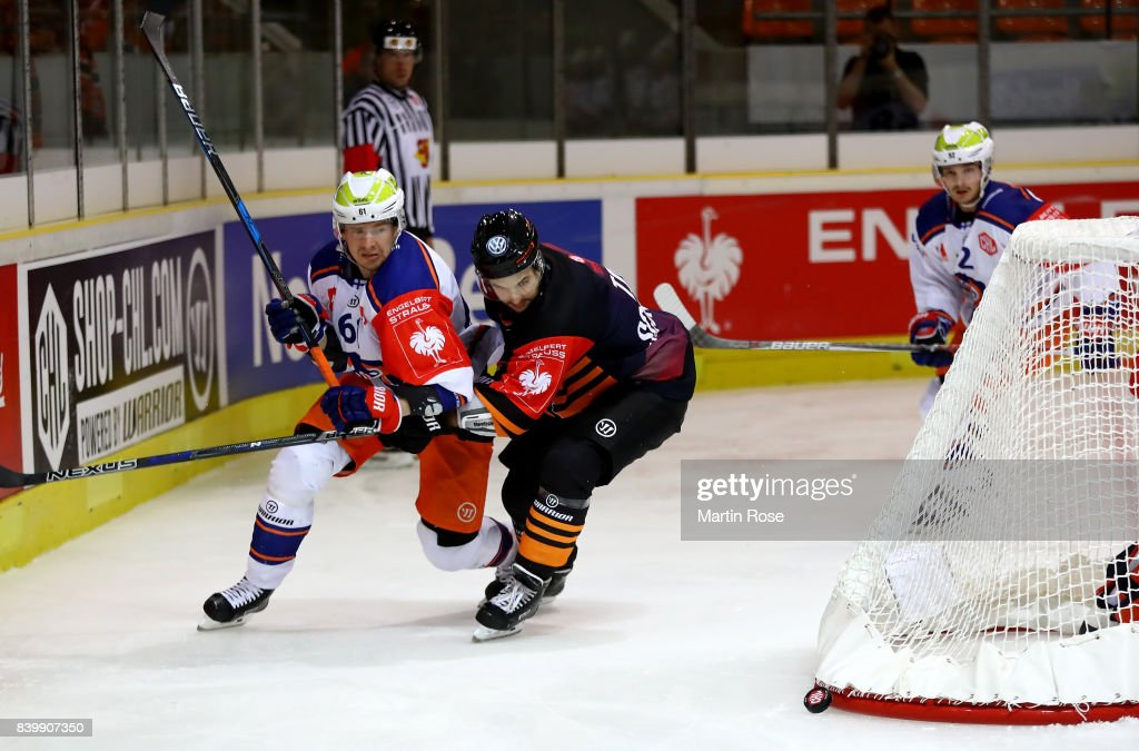Kris Foucault (R) of Wolfsburg and Juhani Jasu of Tampere battle for the puck during the Champions Hockey League match between Grizzlys Wolfsburg and Tappara Tampere at Eis Arena Wolfsburg on August 27, 2017 in Wolfsburg, Germany.
