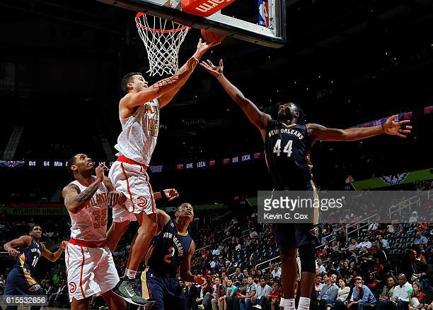 Kris Humphries of the Atlanta Hawks attempts to score on a rebound against Tim Frazier and Solomon Hill of the New Orleans Pelicans at Philips Arena...