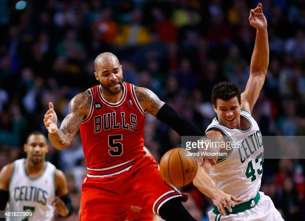 Kris Humphries of the Boston Celtics grabs a loose ball in front of Carlos Boozer of the Chicago Bulls in the first period during the game at TD...