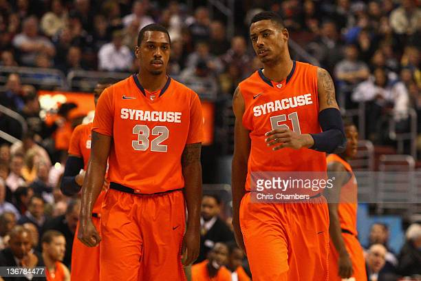 Kris Joseph and Fab Melo of the Syracuse Orange talk as they walk on the court against the Villanova Wildcats at the Wells Fargo Center on January 11...