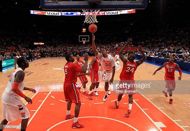 Kris Joseph of the Syracuse Orange drives to the basket against Justin Burrell of the St John's Red Storm during the quarterfinals of the 2011 Big...
