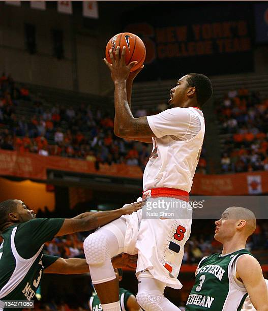 Kris Joseph of the Syracuse Orange puts the ball up to the basket against Darrell Lampley and Austin Harper of the Eastern Michigan Eagles during the...
