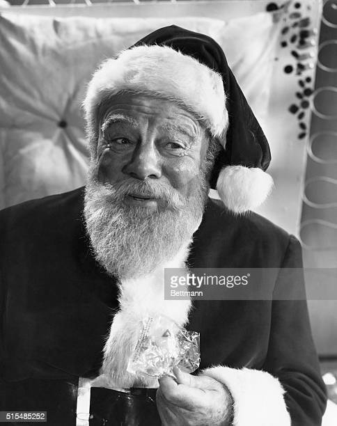 Kris Kringle passes out candy to the kids at Macy's where he plays Santa Claus Miracle On 34th street a 20th century Fox Production