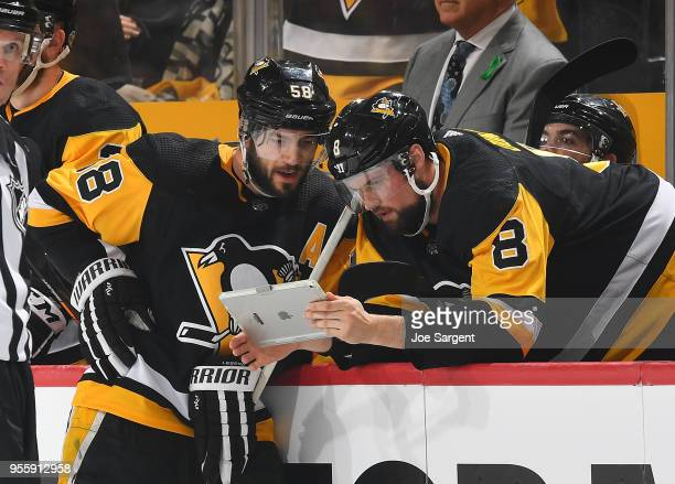 Kris Letang and Brian Dumoulin of the Pittsburgh Penguins watch a replay on an IPAD during the game against the Washington Capitals in Game Four of...