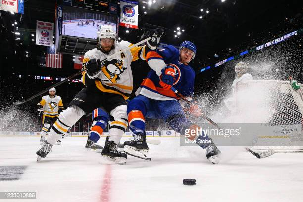 Kris Letang of the Pittsburgh Penguins and Anthony Beauvillier of the New York Islanders chase down a loose puck during the second period in Game...