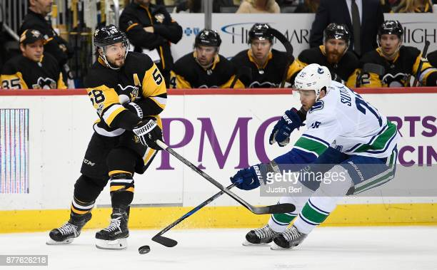 Kris Letang of the Pittsburgh Penguins attempts a pass while under pressure from Brandon Sutter of the Vancouver Canucks in the third period during...