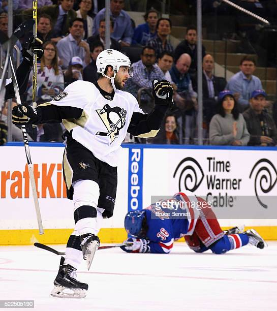 Kris Letang of the Pittsburgh Penguins celebrates his empty net goal at 19:47 of the third period as Mats Zuccarello of the New York Rangers hits the...