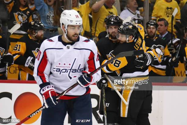 Kris Letang of the Pittsburgh Penguins celebrates his second period goal with Brian Dumoulin behind Chandler Stephenson of the Washington Capitals in...