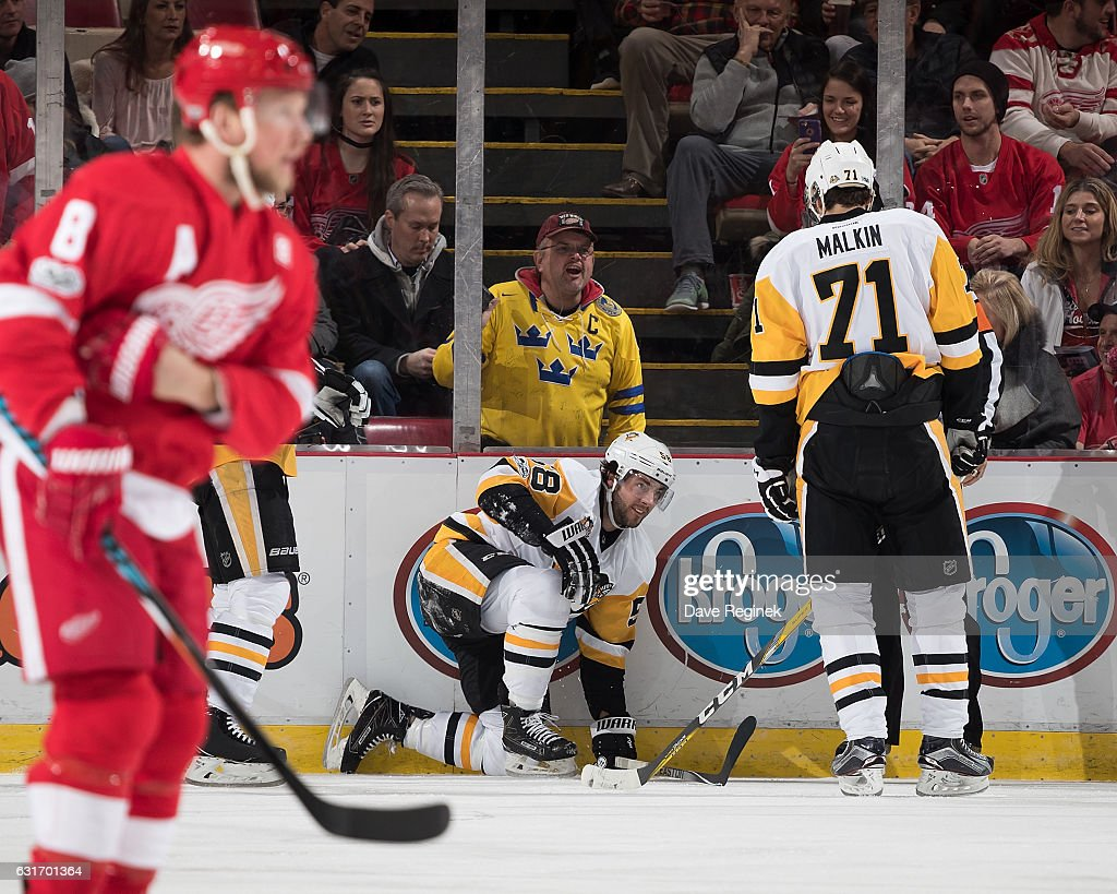 Kris Letang #58 of the Pittsburgh Penguins kneels on the ice after a first period injury while teammate Evgeni Malkin #71 looks over and Justin Abdelkader #8 of the Detroit Red Wings skates by during an NHL game at Joe Louis Arena on January 14, 2017 in Detroit, Michigan.