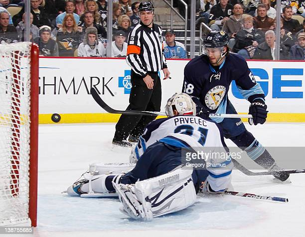 Kris Letang of the Pittsburgh Penguins scores a goal against Ondrej Pavelec of the Winnipeg Jets on February 11, 2012 at Consol Energy Center in...
