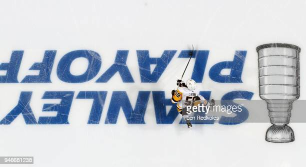 Kris Letang of the Pittsburgh Penguins skates with the puck against the Philadelphia Flyers across the Stanley Cup Playoffs logo on the ice in Game...