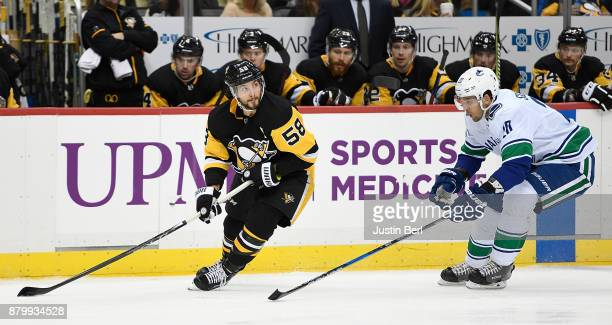 Kris Letang of the Pittsburgh Penguins skates with the puck under pressure from Brandon Sutter of the Vancouver Canucks in the third period during...