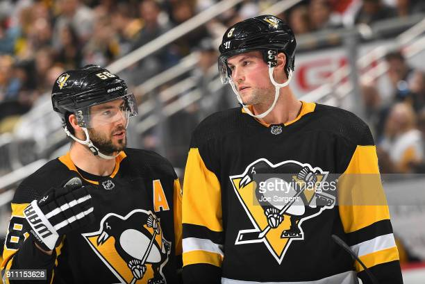 Kris Letang talks with Brian Dumoulin of the Pittsburgh Penguins during the game against the Minnesota Wild at PPG Paints Arena on January 25 2018 in...