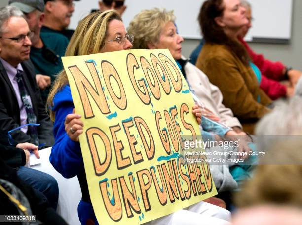 Kris Mendoza of Yorba Linda holds up a sign protesting the Yorba Linda Water District during a district board meeting Thursday night INFORMATION...