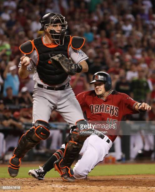 Kris Negron of the Arizona Diamondbacks is forced out at home plate by catcher JT Realmuto of the Miami Marlins during the ninth inning of the MLB...