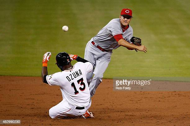 Kris Negron of the Cincinnati Reds turns a double play over Marcell Ozuna of the Miami Marlins during the second inning of the game at Marlins Park...