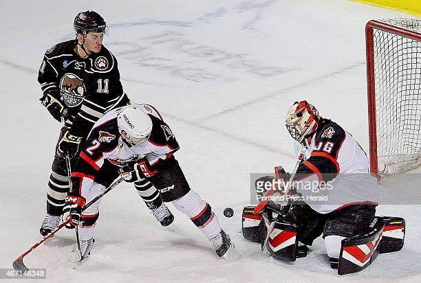 Kris Newbury of the Hershey Bears and Dylan Reese of the Portland Pirates battle in front of the net as Portland goalie Mike McKenna turns the puck...