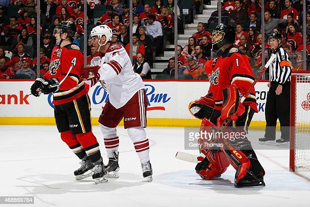 Kris Russell and Jonas Hiller of the Calgary Flames skate against Jordan Szwarz of the Arizona Coyotes at Scotiabank Saddledome on April 7 2015 in...