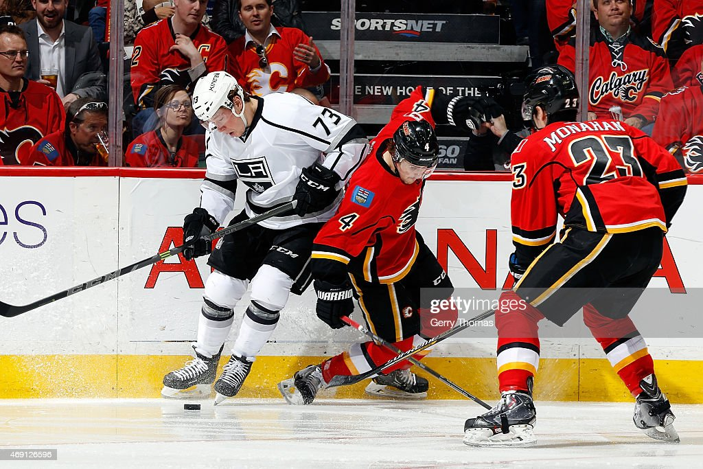 Kris Russell #4 and Sean Monahan #23 of the Calgary Flames skate against Tyler Toffoli #73 of the Los Angeles Kings at Scotiabank Saddledome on April 9, 2015 in Calgary, Alberta, Canada.