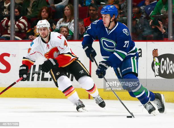 Kris Russell of the Calgary Flames and Shawn Matthias of the Vancouver Canucks skate up ice during their NHL game at Rogers Arena April 13, 2014 in...